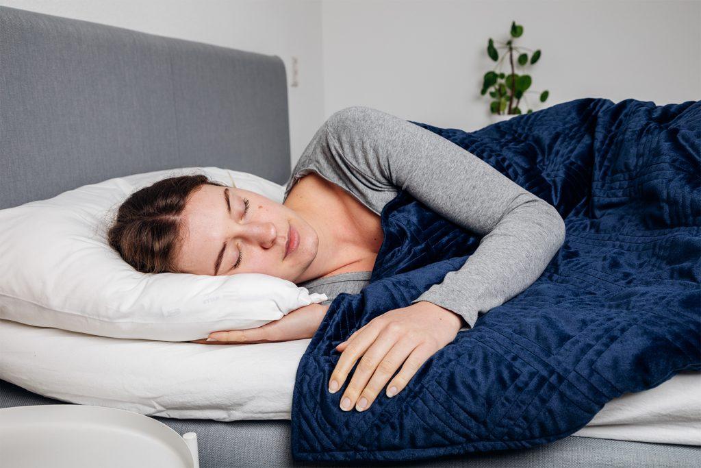 Vrouw ligt onder blauwe verzwaringsdeken in bed