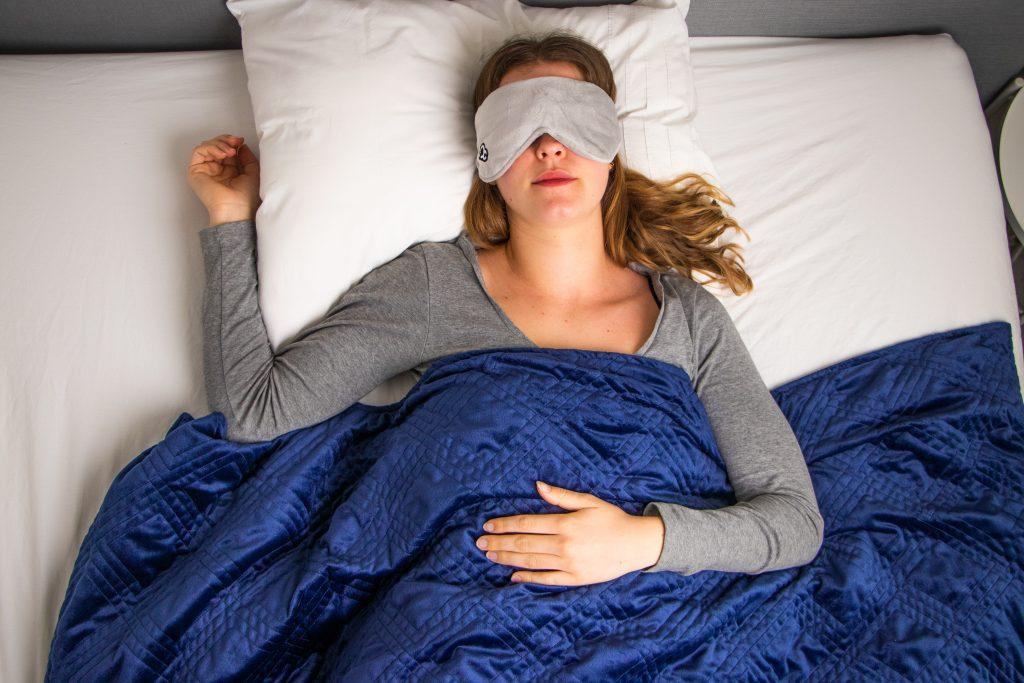 Vrouw op bed met gezichtsmasker en verzwaringsdeken van simply cosy