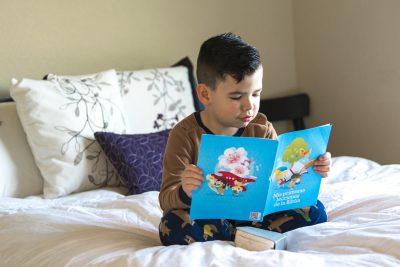Kind zit op een bed boek te lezen